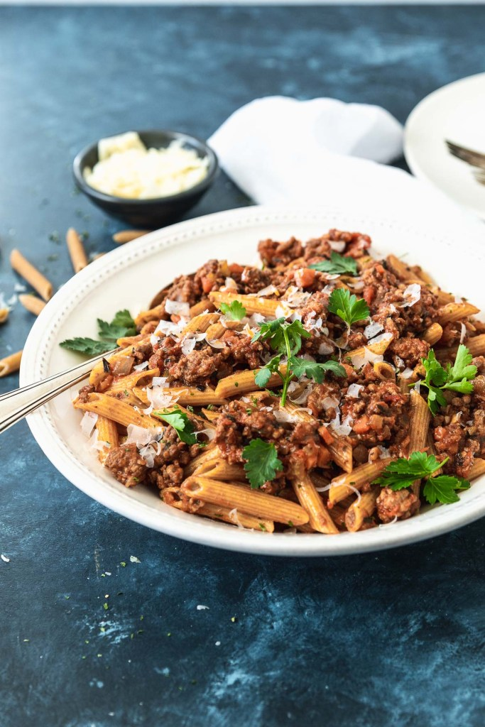 Large white pasta bowl filled with penne and bolognese sauce