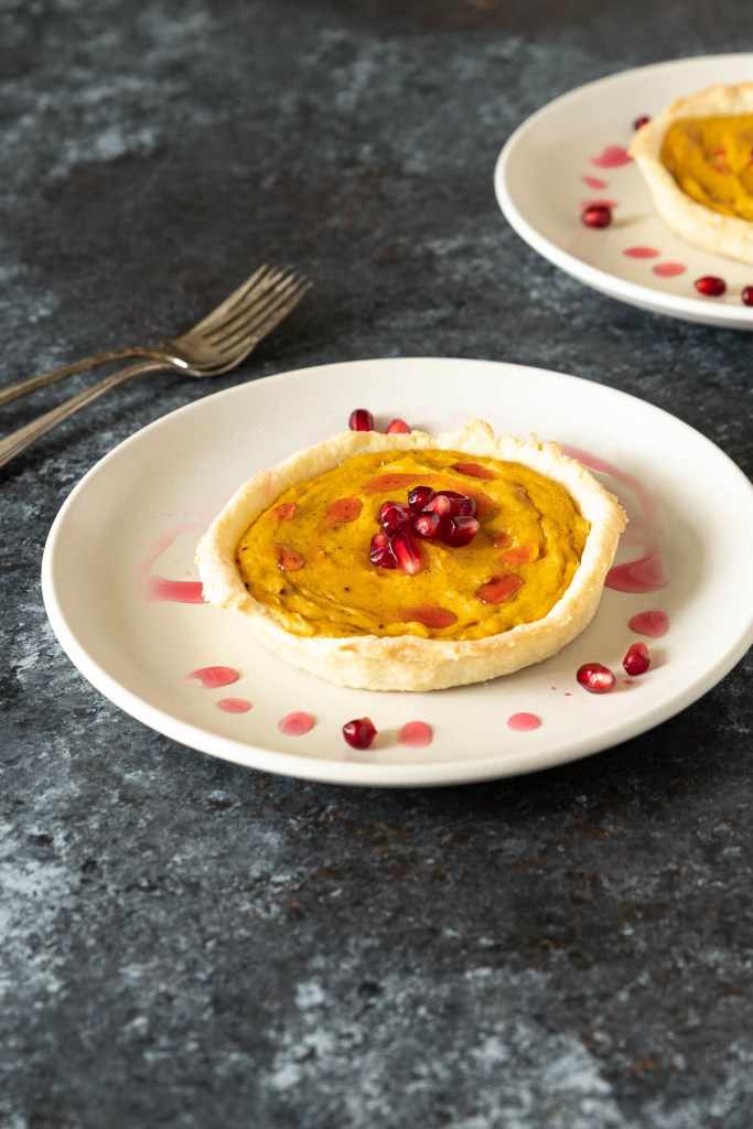 Butternut squash tart topped with pomegranate seeds and simple syrup