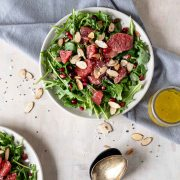 Arugula salad topped with toasted almonds, grapefruit and pomegranate