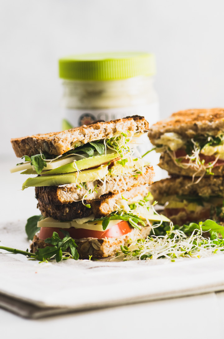 Two halves of a veggie sandwich stacked on top of each other