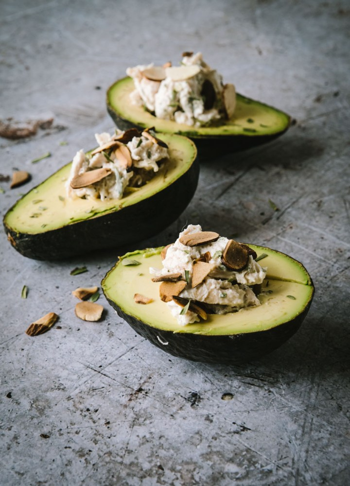 Side angle photo of three avocados stuffed with chicken salad