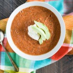 Traditional tomato gazpacho topped with avocado slices and creme fraiche
