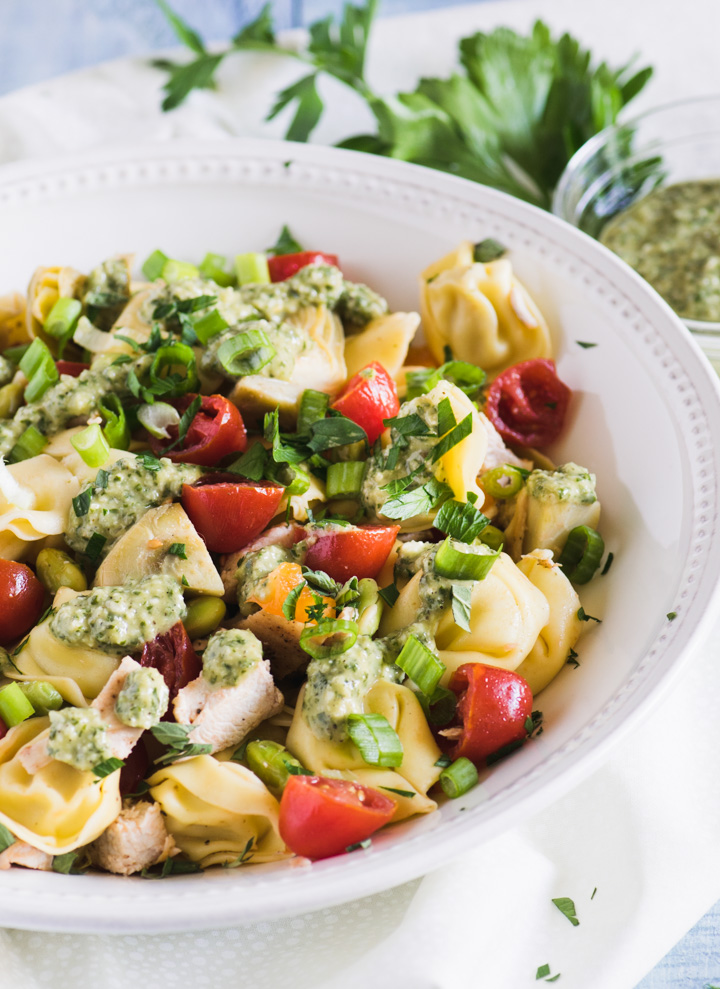 Tortellini pasta salad with pesto dressing in a large white bowl