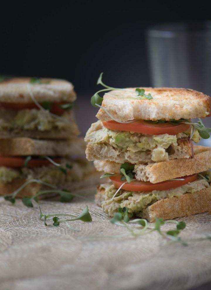 Vegetarian avocado & White bean sandwiches topped with roma tomato