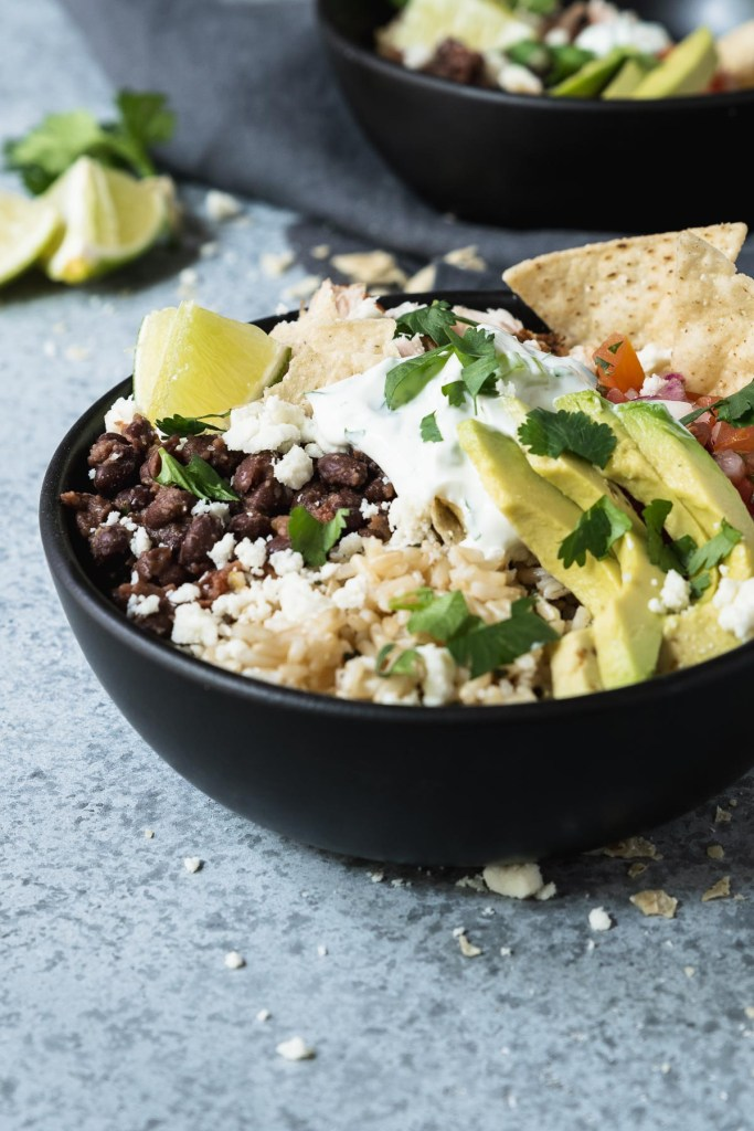 Brown rice bowl topped with shredded chicken, avocado, black beans and pico de gallo