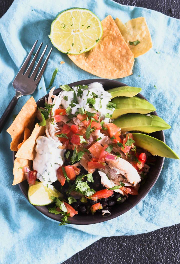 Brown rice burrito bowl topped with chicken, seasoned black beans, pico de gallo and a cilantro lime sauce.