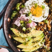 Skillet filled with hash browns that are topped with ham, a poached egg and avocado slices