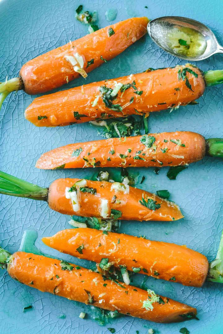 Bright orange steamed carrots with lime gremolata on a teal plate