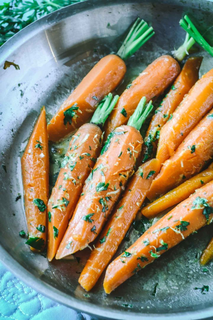 Steamed carrots in stainless steal pan topped with gremolata
