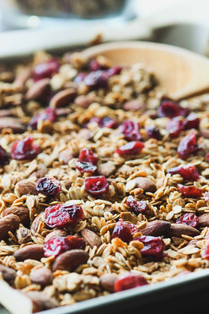 Close up of homemade Granola sprinkled with dried cranberries on a baking sheet