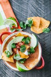 Slow cooker chicken tortilla soup topped with avocado, pico de gallo and lime wedges
