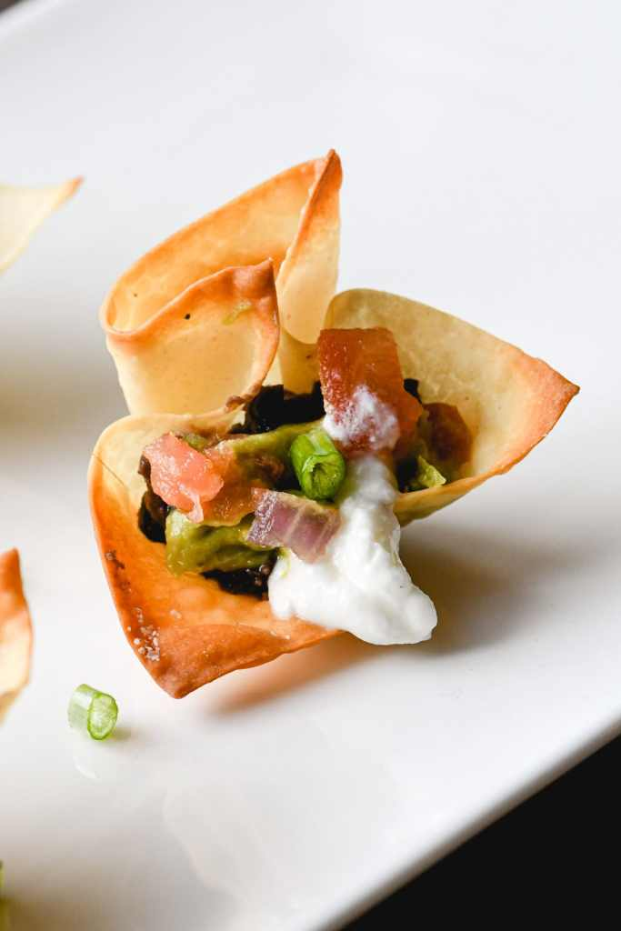 Close up of a wonton cup on a white platter filled with black beans, guacamole and pico de gallo