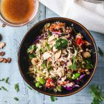 Asian quinoa salad with edamame, cabbage and red pepper in a dark blue bowl