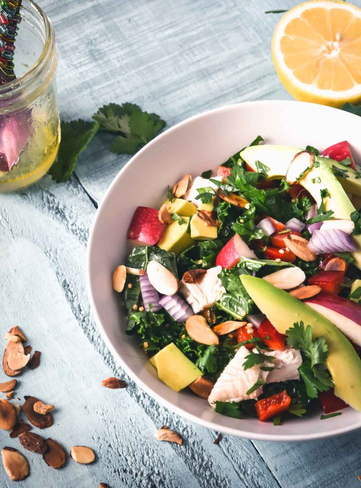 Chopped kale salad topped with avocado, chicken and sliced almonds
