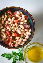 White bean salad with tomatoes and red onions in a dark blue bowl