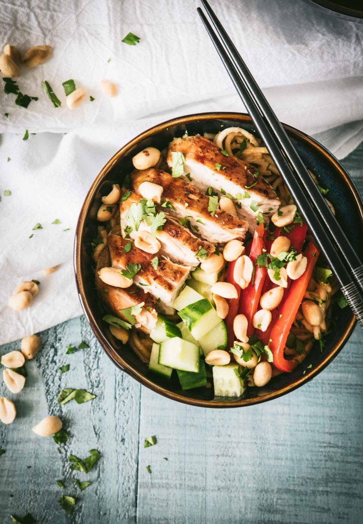 Cold udon noodles in a dark bowl topped with grilled chicken and peanut sauce