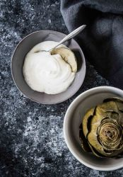 Artichoke dipping sauce with steamed artichoke on a grey background