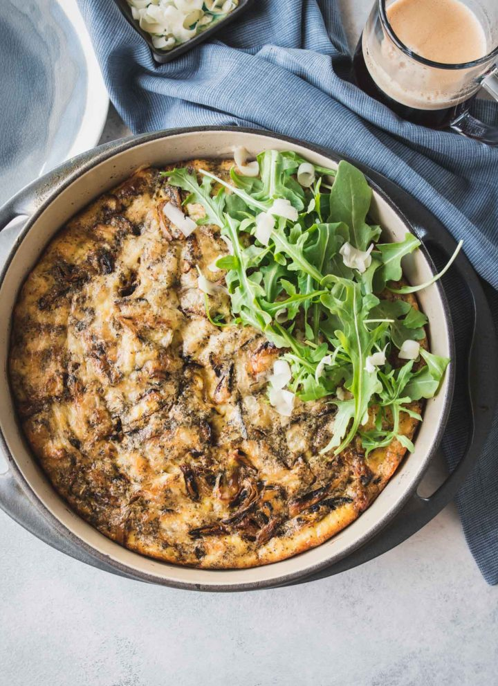 Caramelized onion frittata in a grey cast iron pan