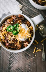 Beef chili topped with sour cream and shredded cheddar photographed from overhead