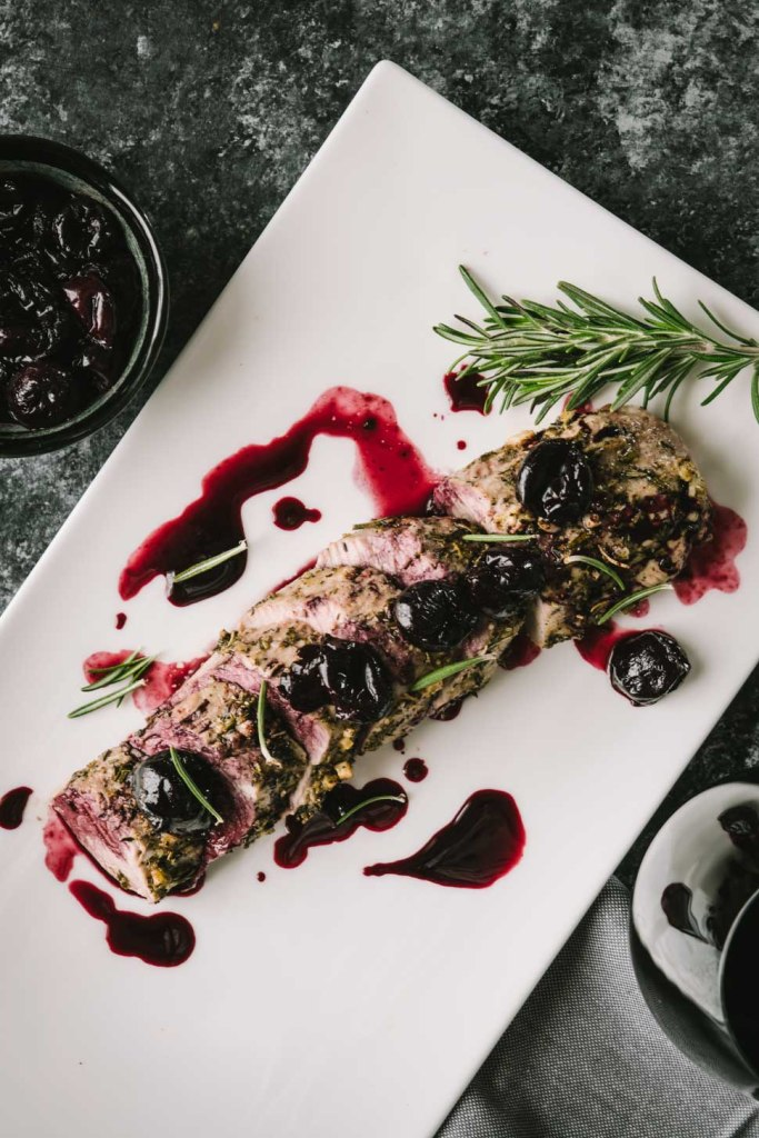 Roasted pork tenderloin topped with cherry merlot sauce shot from overhead