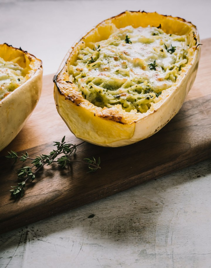 Close up of a half a baked spaghetti squash with cheese and pesto