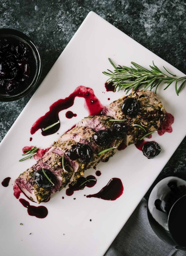 Roasted pork tenderloin topped with cherry sauce on a white platter
