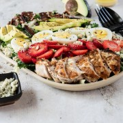 Cobb salad topped with chicken, avocado, bacon and sliced strawberries on a cream platter