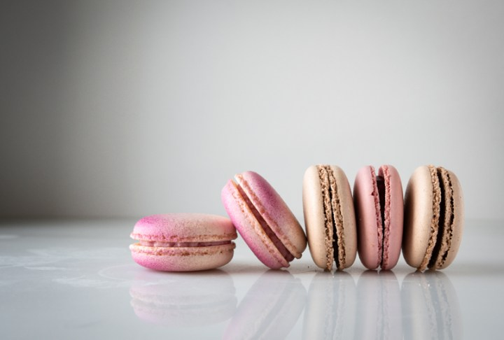 Five pink hued macaroons standing on their sides