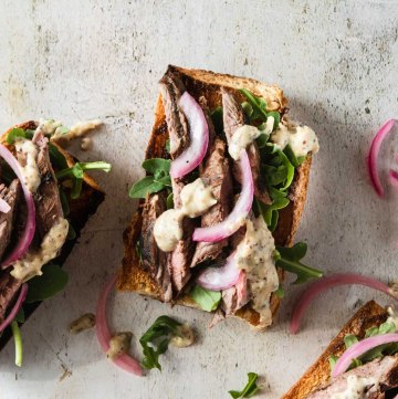 Close up of an open faced steak sandwich on crusty bread topped with bright pink pickled onions