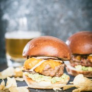 Close up of a southwestern turkey burger slider with potato chips scattered in front