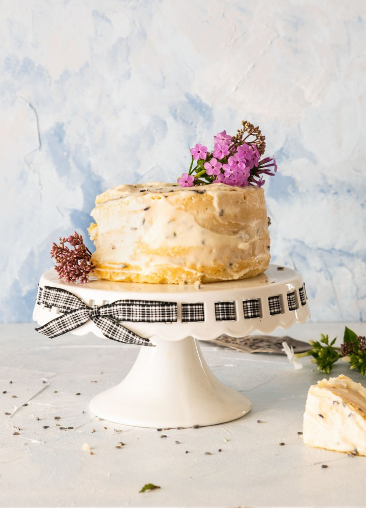 Lemon cake with lavender butter cream on a white cake stand
