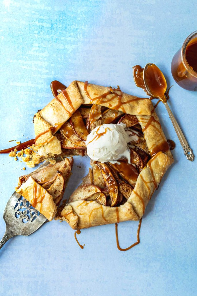 Apple galette topped with vanilla ice cream scoop on a light blue background