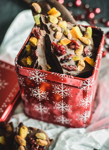 Pieces of chocolate bark in a red holiday gift tin