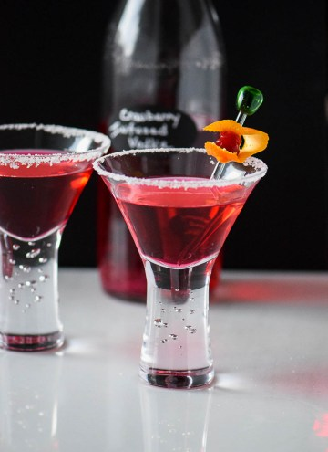 Cranberry Vodka martinis with a bottle of cranberry infused vodka in the background
