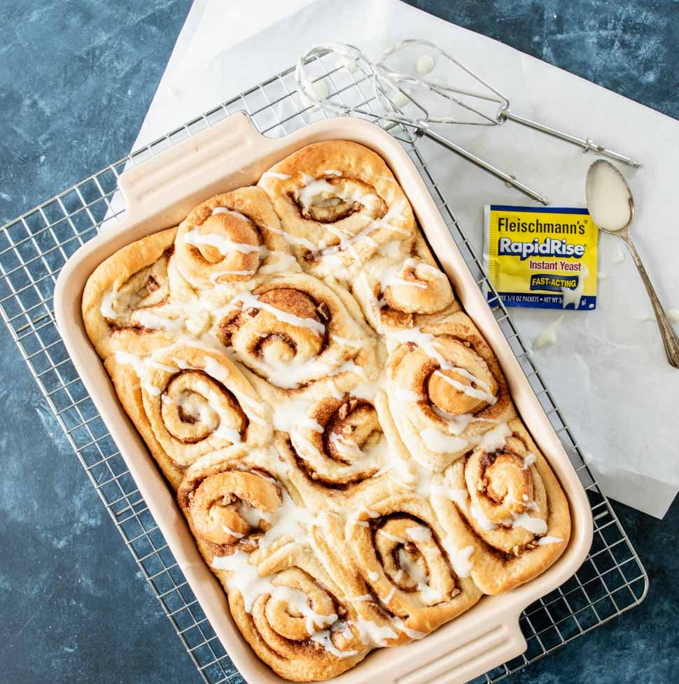 Orange cinnamon rolls in a baking pan drizzled with glaze