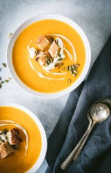 Overhead shot of two white bowls filled with butternut squash soup