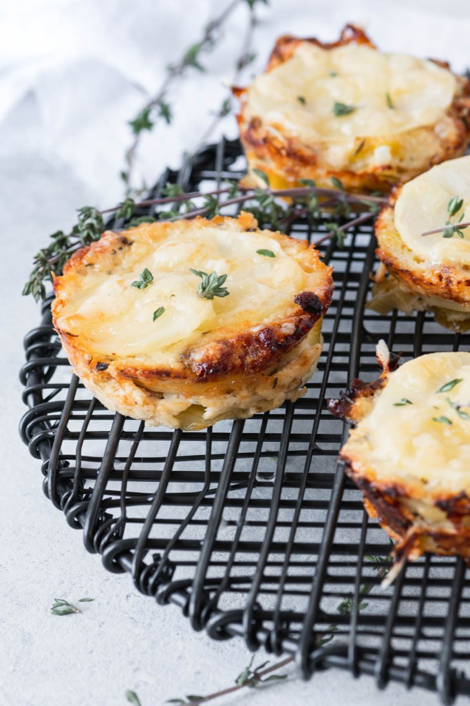 Close up of individual potato gratins sprinkled with fresh thyme