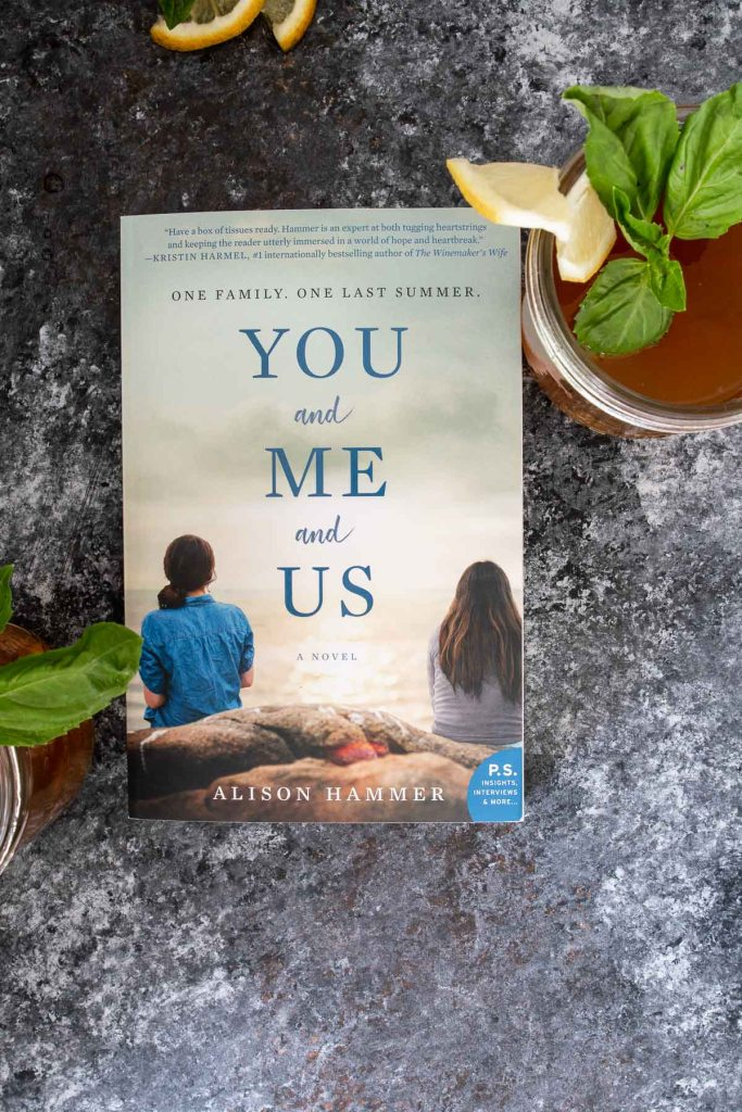 You + Me + Us book with cocktail on the side, shot from overhead