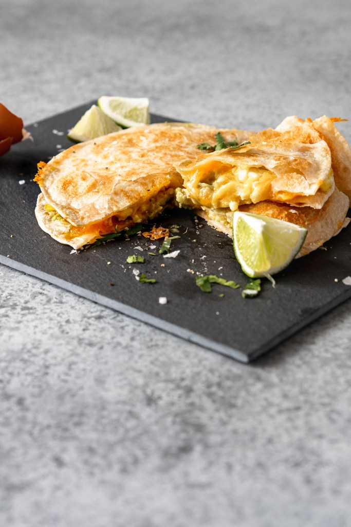 Quesadilla with eggs and avocado, sliced, on a slate board