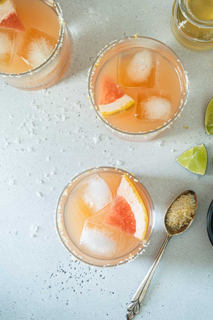 Overhead shot of three grapefruit margaritas in salt rimmed glasses