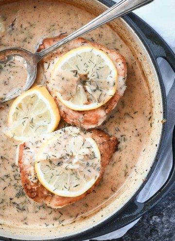 Overhead shot of chicken breasts with lemon sauce in a skillet