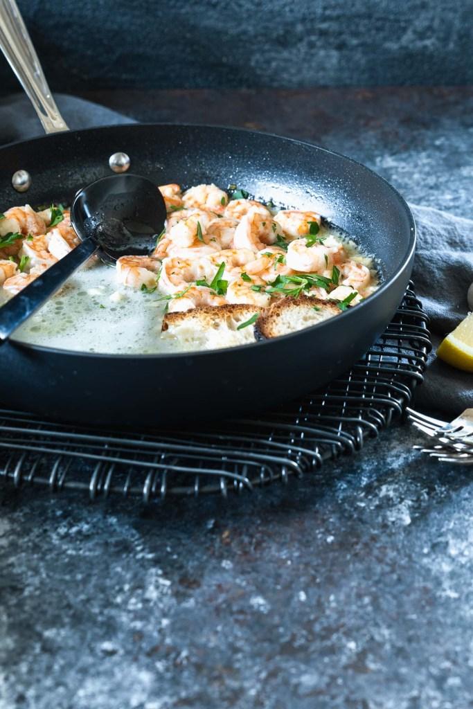 Black pan filled with lemon garlic butter shrimp