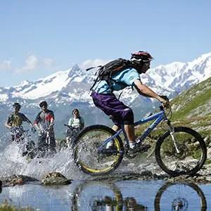 Image de VTT traversant un lac avec figurants en montagne