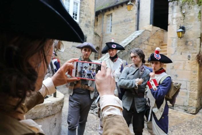 Photo de figurants qui se photographient lors du tournage d'un film sur la révolution à Sarlat en Périgord