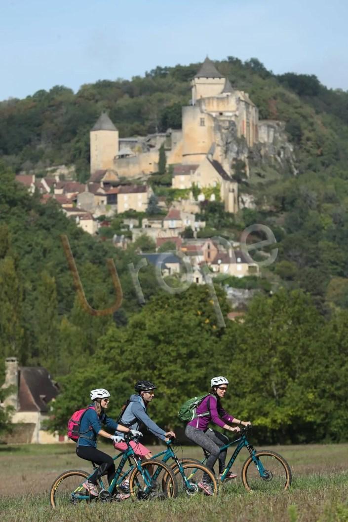 Photo d'un groupe de VTT devant le chateau de Castelnaud-la-Chapelle en Périgord
