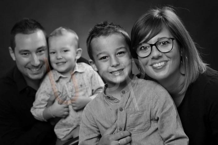 Photo d'une mère et son fils au premier plan et le père avec l'autre fils au deuxième plan