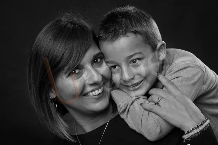 Image en noir et blanc d'une maman avec son fils sur l'épaule