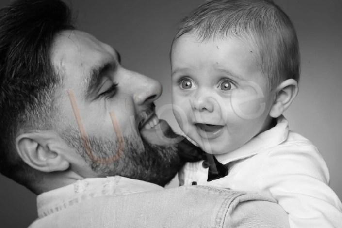 Photo bébé au regard étonné sur l'épaule de son papa