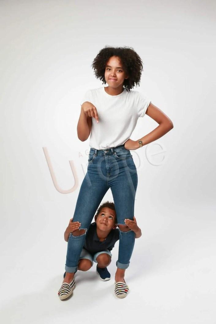 Photo d'une adolescente qui montre son frère à ses pieds