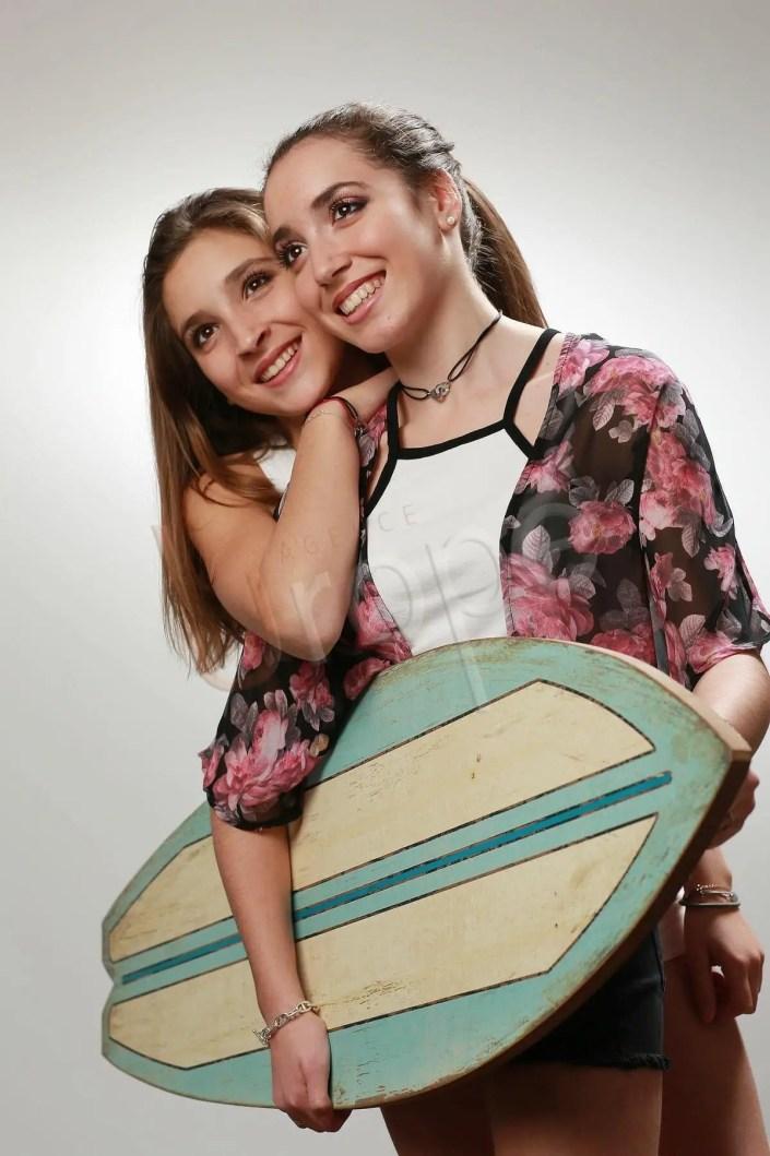 Photo de deux soeurs qui portent un surf en studio pour des tirages-photos
